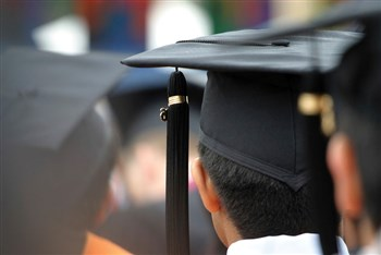 Close-up of man with graduation cap on from behind